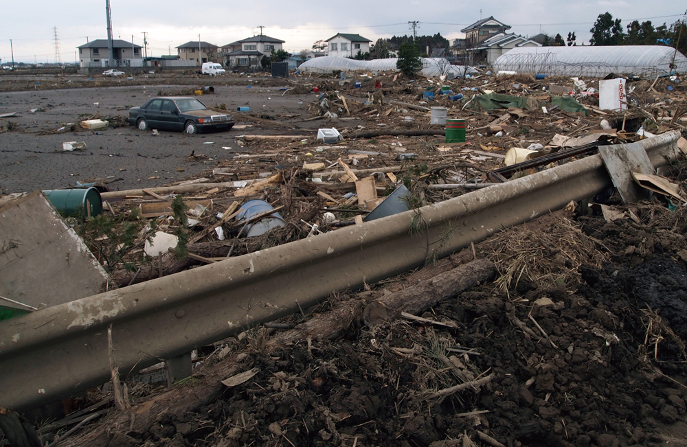 津波でガードレールに溜まる流木やドラム缶
