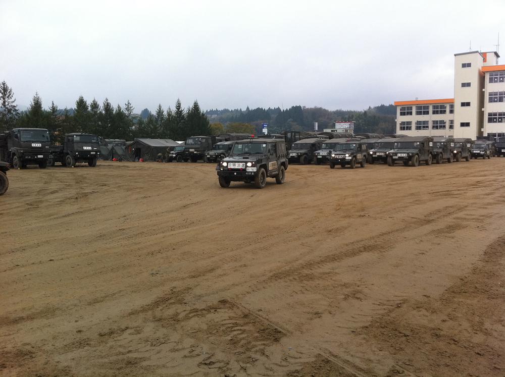 条南中学校校庭から出発する自衛隊の車