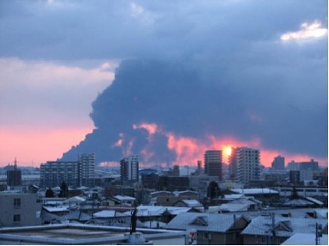 震災翌朝、仙台港の石油コンビナートから立ち上がる黒煙